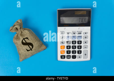 Business and finance taxes concept. A money bag and calculator with text on blue background from top view. Depicts the importance of management about - Stock Photo