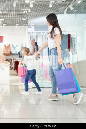 Side view of young attractive mother shopping together with little daughter in mall. Positive girl keeping hand of woman and running in shops. Family choosing and buying new clothes and toys. - Stock Photo