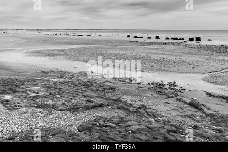 English shoreline along rocky coast and sandy beach on sunny morning in summer with view of sea under blue sky, Fraisthorpe, Yorkshire, UK. - Stock Photo