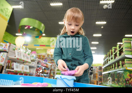 Suprized girl wih open mouth playing with plasticine in big toy store. Little female child enjoying, choosing and buying new cool toys in supermarket. Concept of childhood and joy. - Stock Photo
