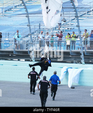 A skydiver from Homestead Air Reserve Base got tangled in the catch fence on turn one when the wind pickup during the singing of God Bless America and pushed him into the fence at the beginning of the  NASCAR Cup Series Championship' at Homestead-Miami Speedway in Homestead, Florida on November 18, 2018.  Photo By Gary I Rothstein/UPI - Stock Photo