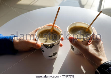Men's hands holding paper disposable cups of coffee on the table in the cafe. Breakfast. - Stock Photo