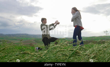 A young couple on the field - A man doing an proposal to his girlfriend - Stock Photo