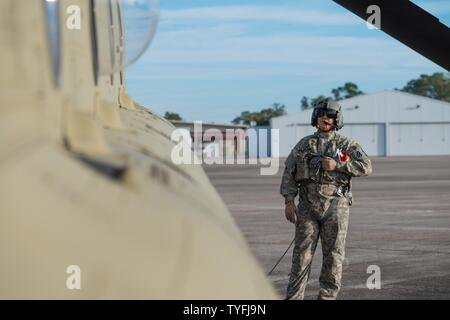 A U.S. Army Chinook crewmember assigned to the 3rd Combat Aviation Brigade prepares for a slingload training mission at Hunter Army Airfield, Nov. 6, 2016. The soldiers are transporting howitzers to a training area on Fort Stewart in support of the 3rd Division Artillery. - Stock Photo