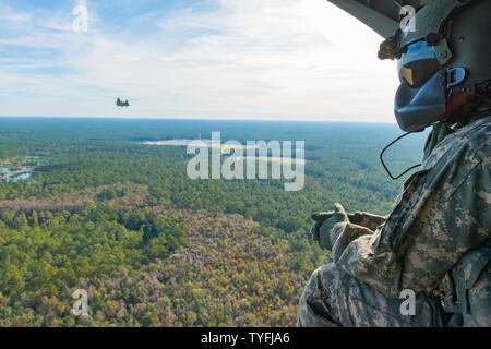 A U.S. Army Chinook crewmember assigned to the 3rd Combat Aviation Brigade observes Chinooks in flight over Fort Stewart during a slingload training mission at Hunter Army Airfield, Nov. 6, 2016. The soldiers are transporting howitzers to a training area on Fort Stewart in support of the 3rd Division Artillery. - Stock Photo