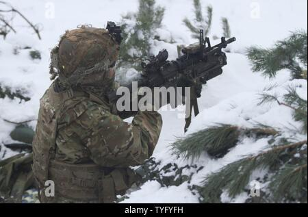 "ADAZI, Latvia – A Paratrooper assigned to Battle Company, 2nd Battalion, 503rd Infantry Regiment, 173rd Airborne Brigade, prepares to fire an M203 grenade launcher from his fighting position during Exercise Steel Shield at Camp Adazi, Latvia, Nov. 7, 2016. Steel Shield partnered U.S. Paratroopers with the Estonian Scouts Battalion, based out of Paldiski, Estonia, to conduct live-fire defensive operations. The ""Sky Soldiers"" of B Co., 2nd Bn., 503rd Inf. Regt., are on a training rotation in support of Operation Atlantic Resolve, a U.S. led effort in Eastern Europe that demonstrates U.S. commitm - Stock Photo"