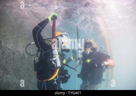Chief Petty Officer Jesse Hamblin, left, and Petty Officer 2nd Class Aaron Brown, both assigned to Underwater Construction Team (UCT) 2's Construction Dive Detachment Bravo (CDDB), conduct diving operations in Diego Garcia, British Indian Ocean Territory, Nov. 8, 2016.  CDDB is performing precision underwater demolition and light salvage to remove obstructions from Diego Garcia's deep draft wharf. CDDB is on the third stop of their deployment, where they are conducting inspection, maintenance, and repair of various underwater and waterfront facilities while under Commander, Task Force (CTF) 75 - Stock Photo