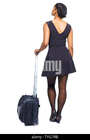 Back view of stylishly dressed black woman with suitcase looking up. Tanned girl in a short dress is leaning on a suitcase. Standing young African Ame - Stock Photo