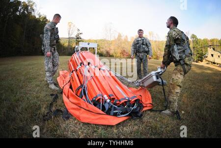 U.S. Army Sgt. Ira Duville, Sgt. Timothy Pinelli, and Spc. Charles Coleman, Jr., Detachment 1, Company B, 2-238th General Support Aviation Battalion, South Carolina Army National Guard, prepare a Bambi-bucket system to be used on a CH-47F Chinook heavy-lift cargo helicopter in Greenville, South Carolina, Nov. 10, 2016. The crew and the aircraft have been tasked to support the South Carolina Forestry Commission in containing a remote fire near the top of Pinnacle Mountain in Pickens County, South Carolina. - Stock Photo