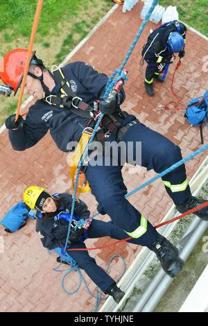 Firefighters Damon Favor and Sara Munaretto assigned to U.S. Army Garrison Italy, practice rappelling at the Army Training Command tower, 34-feet high, during Department of Defense Technical Rope Rescue 1, at Caserma Ederle, Vicenza, Italy, Nov. 10, 2016. Firefighters here received training from instructors from the 435th Construction and Training Squadron, Ramstein Air Base, Germany. Training consisted of a variety of rescue techniques and scenarios including operational risk management, incident management system, ground support for helicopter operations and confined space rescue. This train - Stock Photo