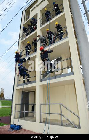 Firefighters assigned to U.S. Army Garrison Italy, rappel to rescue a victim at the 34-foot-high Army Training Command tower, during Department of Defense Technical Rope Rescue 1, at the Caserma Ederle, Vicenza, Italy, Nov. 10, 2016. Firefighters here received training from instructors of the 435th Construction and Training Squadron, Ramstein Air Base, Germany. Training consisted of a variety of rescue techniques and scenarios, including operational risk management, incident management system, ground support for helicopter operations and confined space rescue. This training is vital to keep fi - Stock Photo