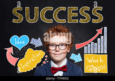 Confident smart kid businessman with Success inscription on chalkboard background. Success, career and develop concept - Stock Photo