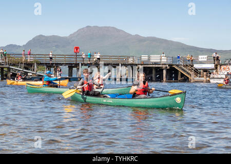 Luss, Loch Lomond, Scotland, UK. 26th June, 2019. UK weather - students from Hillpark Secondary School in Glasgow enjoying brilliant blue skies and bright sunshine this afternoon as they leave the village of Luss paddling on Loch Lomond for their Duke of Edinburgh silver expedition. Credit: Kay Roxby/Alamy Live News - Stock Photo