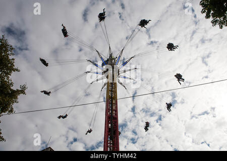 Passengers on a swing ride or chair swing ride with the London Eye in the background, London - Stock Photo