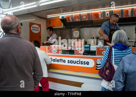 People queueing for galette saucisse (grilled sausage wrapped in crepe)  in the Thursday weekly Market in Dinan, Brittany, France - Stock Photo