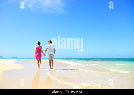 Honeymoon couple holding hands walking on perfect white sand beach. Newlyweds happy in love relaxing on summer holidays in sunny tropical paradise destination. Travel vacation concept. - Stock Photo