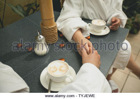 A couple in bathrobes holding hands, drinking coffee while relaxing in the Spa, close-up. Hands of lovers on the background of a wooden table. Guy hol - Stock Photo