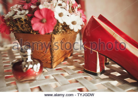 Wedding red designer bride shoes, perfume bottle and decorative flowers in a basket on the coffee table. Women's new luxury modern fashion shoes made - Stock Photo