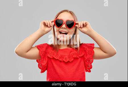 happy preteen girl with heart shaped sunglasses - Stock Photo