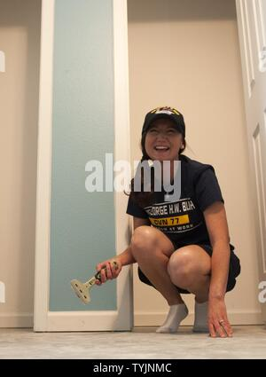 (COLLEGE STATION, Texas) Petty Officer 1st Class Joanna Waugh, 2016 Senior Sailor of the Year for the aircraft carrier USS George H.W. Bush (CVN 77), scrapes the foundation of a home during a Habitat for Humanity project in College Station, Texas. The project is part of a two-day namesake trip to Texas where Sailors engaged with the local community about the importance of the Navy.
