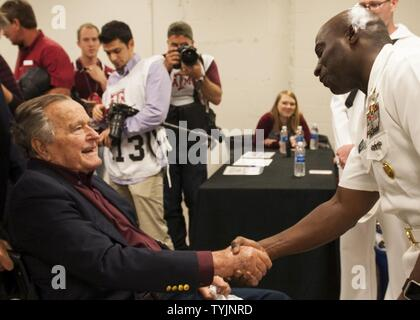 COLLEGE STATION, Texas (Nov. 16, 2016) USS George H.W. Bush (CVN 77) Command Master Chief Huben Phillips meets former president George H.W. Bush during a military appreciation football game at Texas A&M University. The game is part of a two-day namesake trip to Texas where Sailors engaged with the local community about the importance of the Navy in defense and prosperity.
