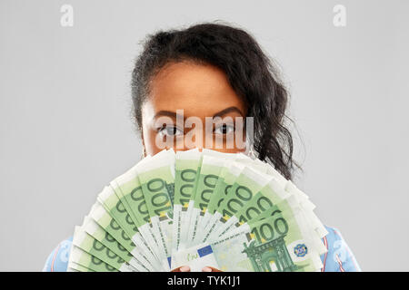 african american woman hiding face behind money - Stock Photo
