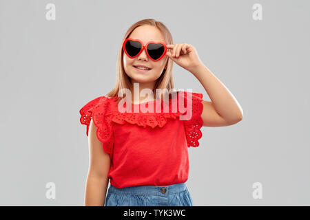 smiling preteen girl with heart shaped sunglasses - Stock Photo
