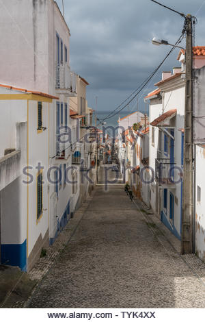 Long steep narrow cobbled street between whitewashed houses leading down to the ocean in a coastal town - Stock Photo