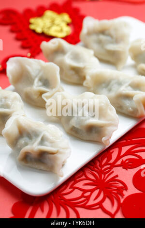 Spring Festivl dumplings and paper-cut on red background - Stock Photo
