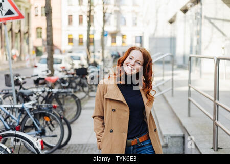 Cute friendly confident young redhead woman walking through town in a trendy trench coat smiling happily at the camera as she passes a row of parked b - Stock Photo