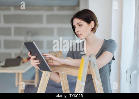 Serious concerned young woman using a tablet as she leans on a stepladder in an unpainted room during renovations - Stock Photo