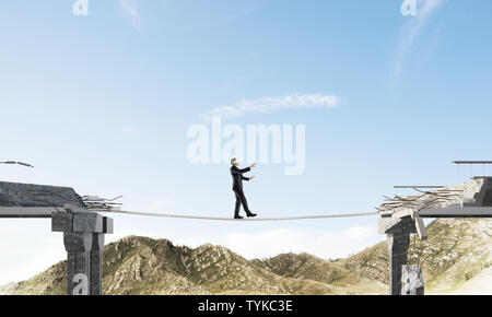 Businessman walking blindfolded on rope above huge gap in bridge as symbol of hidden threats and risks. Skyscape and nature view on background. 3D ren - Stock Photo