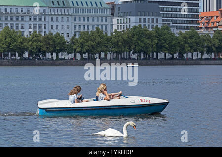 pedal boat on lake Inner Alster with the street Neuer Jungfernstieg in the background , Hamburg, Germany - Stock Photo