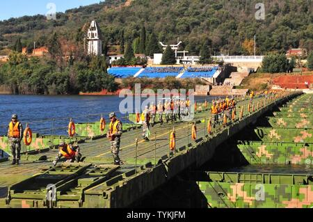 Soldiers from the 130th Engineer Brigade, 8th Theater Sustainment and People's liberation Army cross a bridge they constructed together during the 12th US-China Disaster Management Exchange, November 18, Kunming, Yunnan province, People's Republic of China. The bridge enabled them to evacuate civilians stranded on an island as part of a fictional earthquake scenario in which the two armies' were responding as part of the recovery efforts. The annual United States Army Pacific (USARPAC) Security Cooperation event with the People's Liberation Army (PLA) is an opportunity to share Humanitarian As - Stock Photo