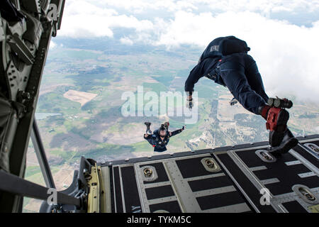 U.S. Air Force Academy Wings of Blue team members Steve Rumsey and Trevor Pratt, , leap off of the C-130 Hercules ramp from 7,700 feet to the ground bellow during the 2019 Skyfest Open House and Airshow performance at Fairchild Air Force Base, Washington, June 22, 2019. Skyfest 2019 offered a unique view of Team Fairchild's role in enabling Rapid Global Mobility for the U.S. Air Force. The show featured more than 13 aerial acts and 16 static display aircraft, as well as other attractions and displays. (U.S. Air Force photo by Airman 1st Class Whitney Laine) - Stock Photo