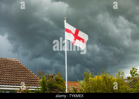 English flag of St George's Cross on top of a flagpole, next to a house roof, standing out against the dark grey clouds of a stormy sky. England, UK. - Stock Photo