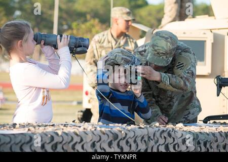 3rd Infantry Division family members takes peer through optics at a static display during Marne Week on Fort Stewart Nov. 15, 2016. Marne Week is a week of special activities for soldiers and family members in celebration of the 99th anniversary of the 3rd Infantry Division. - Stock Photo