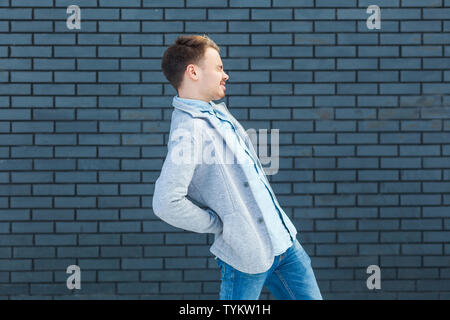 Back or kidney pain profile side view portrait of sick or tired handsome young blonde man in casual style standing and holding his painful back. indoo - Stock Photo