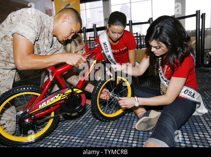 Marine Blake Johnson of Redding, PA, helps out Miss USA contestants Angelina Kayyalaynen, center, of Washington and Brittany Lee Thelemann of Minnesota assemble a bicycle during the USO Build a Bike event where bikes are assemble and donated to military families at Pier 88 on May 26, 2011 in New York City.    UPI /Monika Graff. - Stock Photo