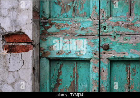 entrance door of an old and damaged residential building - Stock Photo