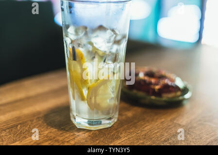 Cold lemonade with ice and lemons in a tall glass with a disposable tube. Chocolate donut with dressing. Delicious and unhealthy breakfast. - Stock Photo