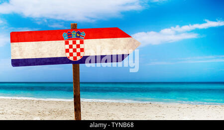 Croatia flag on wooden table sign on beach background. There is beach and clear water of sea and blue sky in the background. - Stock Photo