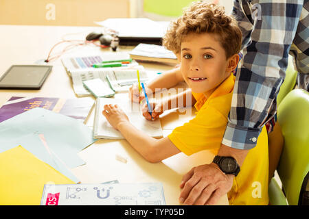 Doing an exercise. Positive cute boy smiling while writing in his textbook - Stock Photo