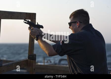 GULF (Nov. 19, 2016) Petty Officer 3rd Class Trevor Philpot, assigned to the guided-missile destroyer USS Nitze (DDG 94), participates in an M9 pistol qualification. Philpot serves onboard Nitze as an electronics technician and is responsible for maintaining, repairing and calibrating shipboard electronic equipment. Nitze, deployed as part of the Eisenhower Carrier Strike Group, is supporting maritime security operations and theater security cooperation efforts in the U.S. 5th Fleet area of operations. - Stock Photo