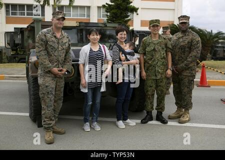 A family poses with Marines and a Japan Ground Self Defense Force service member next to a Humvee Nov. 20, 2016 during the JGSDF Festival on Camp Naha, Okinawa, Japan. The festival celebrated the 6th anniversary of the 15th brigade and the 44th anniversary of Camp Naha. Marines with Combat Assault Battalion, 3rd Marine Division, III Marine Expeditionary Force brought the Humvee, a Light Armored Vehicle and an Assault Amphibious Vehicle for display. Attendees of the festival were able to take photos with the Marines and their vehicles. - Stock Photo