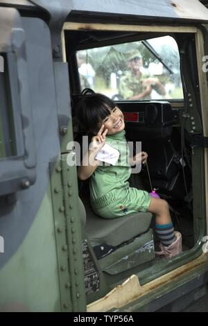 An Okinawa resident poses inside a Humvee Nov. 20, 2016 during the Japan Ground Self Defense Force Festival on Camp Naha, Okinawa, Japan. The festival celebrated the 6th anniversary of the 15th Brigade and the 44th anniversary of Camp Naha. Marines with Combat Assault Battalion, 3rd Marine Division, III Marine Expeditionary Force brought the Humvee, a Light Armored Vehicle and an Assault Amphibious Vehicle for display. Attendees of the festival were able to take photos with the Marines and their vehicles. - Stock Photo