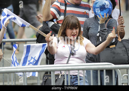 A woman holds up the middle finger at protesters who hold up signs as participants march up Fifth Avenue carrying Israeli Flags and balloons at the Celebrate Israel Parade in New York City on May 31, 2015.   Photo by John Angelillo/UPI - Stock Photo