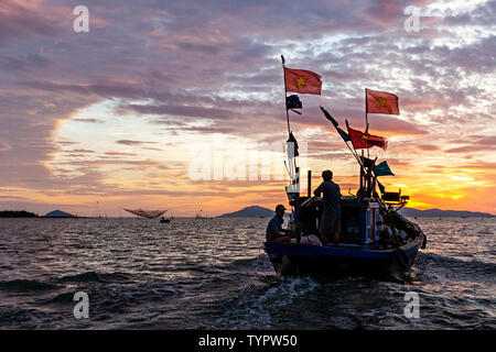 Local fishermen on their way to the fishing grounds. In background: Traditional hanging fishing nets in the sea, at the entrance to Thu Bon River, Hoi - Stock Photo