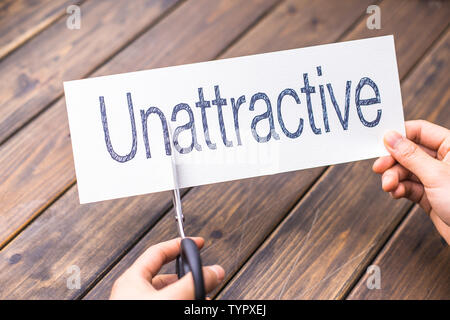 woman cuts white paper with word unattractive on table - Stock Photo