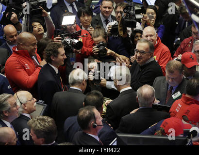 CEO Fiat Chrysler Automobiles Sergio Marchionne and Fiat Chrysler chairman John Elkann ring the bell as they stand on the floor of the NYSE on the first day of public trading of Ferrari at the New York Stock Exchange on Wall Street in New York City on October 21, 2015. The company's stock priced its initial public offering at $52 a share after the market close on Tuesday, with sources saying the demand for shares was 'well oversubscribed.' The price was at the top of the previously indicated range of $48 to $52 per share. Ferrari RACE shares were trading at $58.18 up almost 10 percent Wednesda - Stock Photo